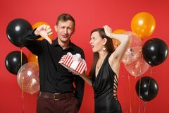 Les couples contrariés dans des vêtements noirs tiennent le boîte-cadeau célébrant la fête de vacances d'anniversaire sur l'air r photo stock