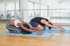 Les couples convenables dans les childs posent sur des tapis d'exercice Images stock