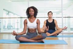 Les couples convenables se reposant dans le lotus posent dans le studio de forme physique Image stock