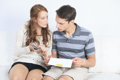 Les couples craintifs faisant leurs comptes se sont reposés sur un divan image libre de droits
