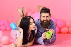 Les couples détendent dans le matin avec du café Couples en café de boissons d'amour dans le lit Homme et femme dans des vêtement Photos libres de droits