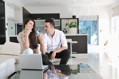 Les couples détendent et travaillent sur l'ordinateur portable à la maison image stock