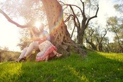 Les couples détendent sous l'arbre Style de beaux-arts Jardin olive Images stock