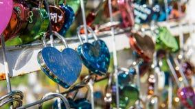 Les couples d'amour ferment à clef accrocher sur le rail photo stock