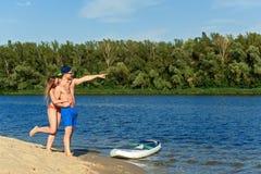 Les couples d'amusement de plage tiennent dessus la PETITE GORGÉE de panneau de palette Photo libre de droits