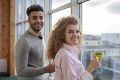 Les couples d'hommes d'affaires tiennent la pause-café de tasses dans des collègues de centre de Coworking se tenant dans la fenê photographie stock libre de droits