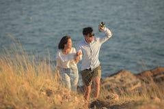 Les couples d'un plus jeune homme et d'une femme dans des vacances de détente d'amour se surpassent Images stock