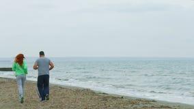 Les couples d'une cinquantaine d'années pulsant sur le bord de la mer échouent pendant le matin Style de vie sain banque de vidéos