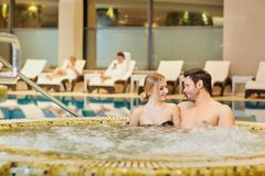 Les couples dans des maillots de bain dans la station thermale de repos de piscine centrent Photo libre de droits
