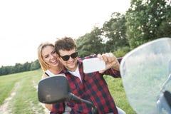 Les couples dans l'amour appréciant un vélo de quadruple montent dans la campagne Photographie stock libre de droits