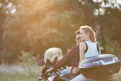 Les couples dans l'amour appréciant une motocyclette montent dans la campagne Photos stock
