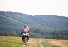 Les couples dans l'amour appréciant une motocyclette montent dans la campagne Image libre de droits