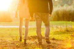 Les couples dans l'amour en automne garent avoir l'amusement au coucher du soleil Images stock