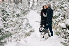 Les couples dans l'amour et le chien de traîneau sibérien poursuivent la marche dans la forêt neigeuse d'hiver Photo stock