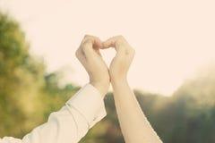 Les couples dans l'amour faisant un coeur forment avec leurs mains dehors Photos stock