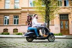 Les couples dans l'amour montant une motocyclette, un type beau et une jeune femme sexy voyagent Image stock