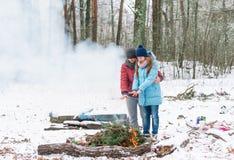 Les couples dans l'amour près du feu pendant l'hiver se garent Photo libre de droits