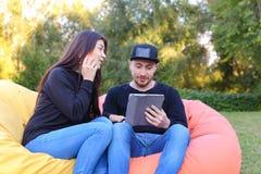Les couples dans l'amour se reposent et parlent dans des fauteuils, prises de type à disposition électr. Photographie stock libre de droits