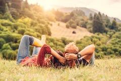 Les couples dans l'amour se reposent sur la colline verte dans le côté de pays Photos stock