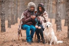 Les couples dans l'amour se reposent dans une forêt couverte dans une couverture, thé de boissons des tasses en métal Un chien se Photos libres de droits