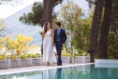 Les couples dans l'amour se sont juste mariés, et la promenade heureuse par le territoire du club national, communiquent et Photographie stock libre de droits