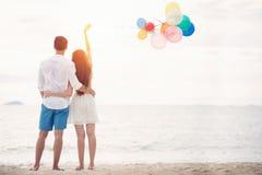 Les couples dans l'amour se tiennent sur la plage avec le bolloon Image stock