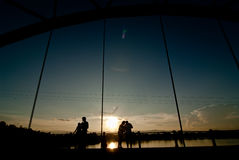 Les couples dans l'amour silhouettent juger des mains en forme de coeur sur le pont a Images libres de droits