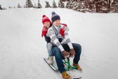 Les couples dans l'amour sledding pendant l'hiver se garent Habillé dans des chapeaux, des mitaines et l'écharpe de knit Photographie stock libre de droits