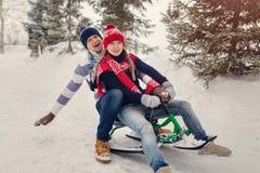 Les couples dans l'amour sledding pendant l'hiver se garent Habillé dans des chapeaux, des mitaines et l'écharpe de knit Photo stock