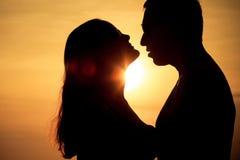 Les couples dans l'amour soutiennent la silhouette légère sur la mer Photographie stock