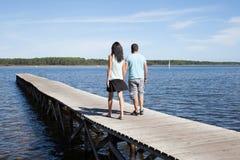 les couples dans l'amour dans les vacances marchent sur la plage de lac de ponton Photos stock