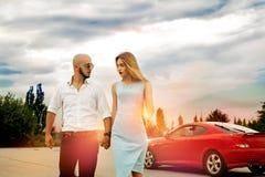 Les couples dans l'amour vont à partir d'une voiture de sport Image stock