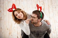 Les couples dans la fausse pose de klaxons de cerfs communs ont l'amusement au-dessus du fond en bois Image libre de droits