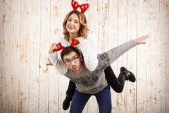 Les couples dans la fausse pose de klaxons de cerfs communs ont l'amusement au-dessus du fond en bois Photographie stock libre de droits