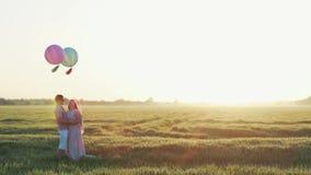 Les couples dans le domaine avec de l'hélium ont coloré des boules étreignant et embrassant clips vidéos