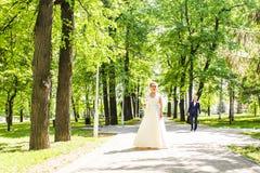 Les couples dans le mariage attire avec un bouquet des fleurs et la verdure est dans les mains contre le contexte du jardin, Photographie stock