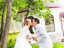 Les couples dans le mariage attire avec un bouquet des fleurs et la verdure est dans les mains, les baisers de jeunes mariés Photographie stock