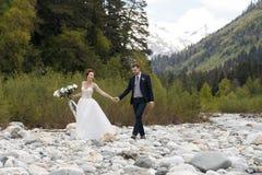 Les couples dans le mariage attire avec un bouquet des fleurs et les verts est aux mains d'une cascade au coucher du soleil, la j Photos stock