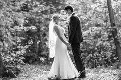 Les couples dans le mariage attire avec un bouquet des fleurs, jeunes mariés dehors Image libre de droits