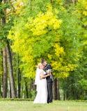 Les couples dans le mariage attire avec un bouquet des fleurs, jeunes mariés dehors Photographie stock