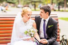 Les couples dans le mariage attire avec un bouquet des fleurs, jeunes mariés dehors Photographie stock libre de droits