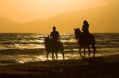 Les couples de cavalier de cheval au coucher du soleil échouent, à côté de la mer Photographie stock libre de droits