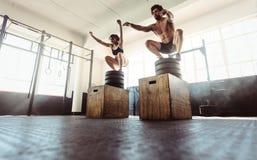 Les couples de forme physique faisant une boîte s'accroupissent au gymnase image stock