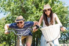 Les couples de hippie sur un vélo montent en parc Image libre de droits