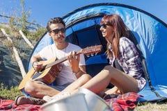 Les couples de jeunes amants ont plaisir à jouer la guitare Images libres de droits