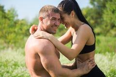Les couples de jeunes sportifs étreignent et embrassent dehors après séance d'entraînement Photo stock