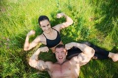 Les couples de jeunes sportifs se trouvent sur l'herbe verte après séance d'entraînement dehors Image stock