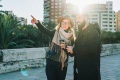 Les couples de jeunes touristes, amis marchent le long de la rue de ville, buvant du café La fille se dirige à quelque chose Photo stock