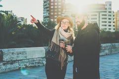Les couples de jeunes touristes, amis marchent le long de la rue de ville, buvant du café La fille se dirige à quelque chose Photographie stock