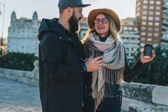 Les couples de jeunes touristes, amis marchent le long de la rue de ville, buvant du café tandis qu'ils regardant heureusement l' Photographie stock
